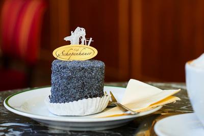 robertkalb photographien Kulinarik: Cafe Schopenhauer, eine Mohn-Preiselbeertorte mit Melange auf dem Tisch.