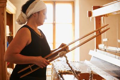 Barbara Schmidt in der Werkstatt Wollschmiedn beim Teppich weben. Das einzigartige Wolltattoo entsteht durch eine Kombination von Weben und Filzen.