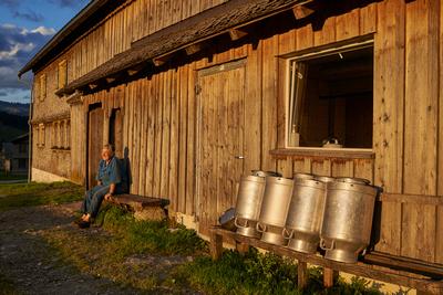 Auf der schönen Vorsäss-Alpe Schönenbach sitzt eine Bäuerin im letzten Abendlicht vor dem Haus auf der Bank.